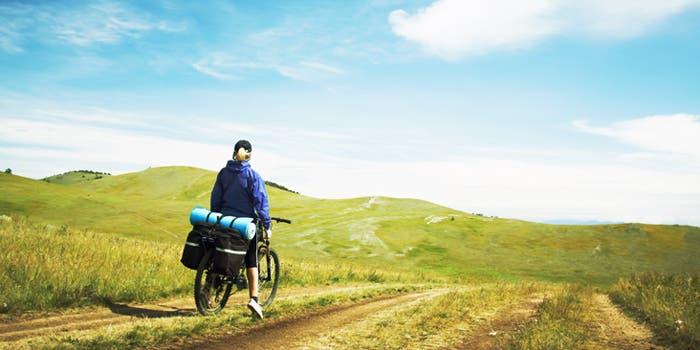 Mujer en bicicleta en un camino de campo