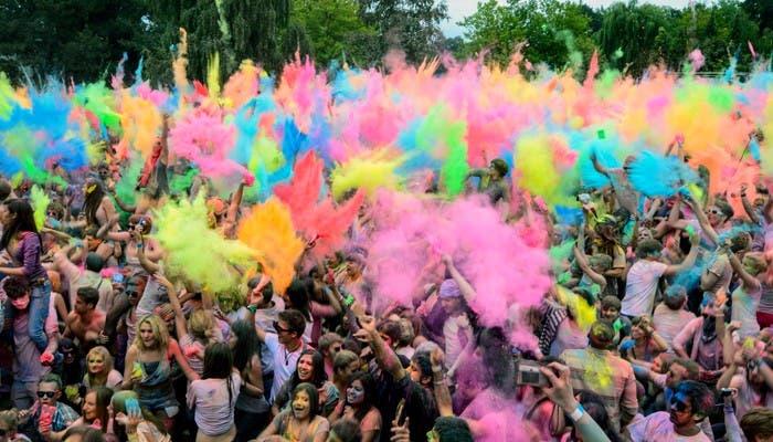Multitud de gente tirándose globos de colores