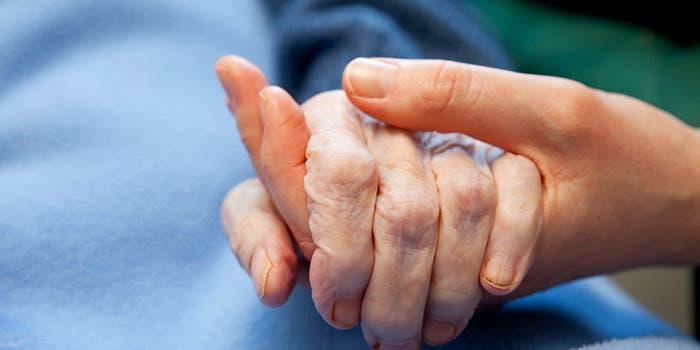 Mano joven sosteniendo una mano arrugada