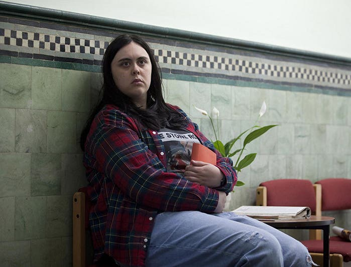 Rae sentada en los bancos del psiquiátrico