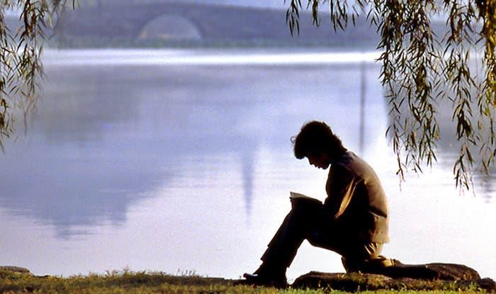 Joven leyendo en la orilla de un río