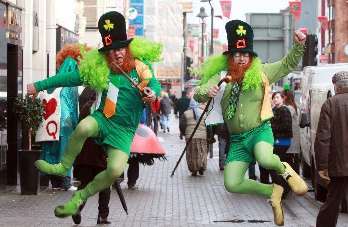 Hombres disfrazados de San Patricio saltando en la calle