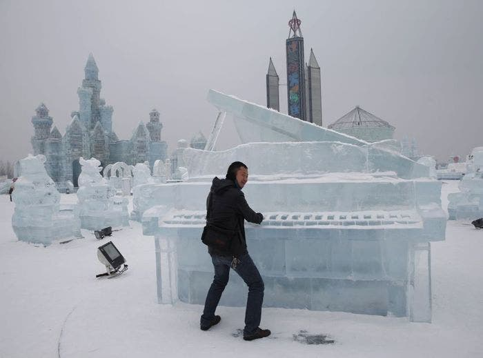 Turista junto a un piano realizado en hielo en la ciudad de Harbin